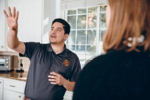 restoration tech talking to customer in kitchen